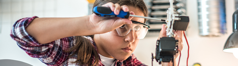 Image of a grade-school aged boy in a classroom with safety goggles on, using a screwdriver to work on a small mechanical device.