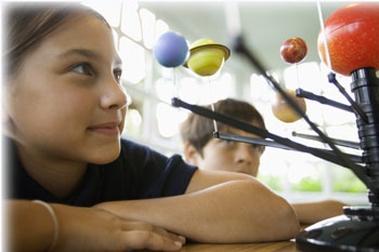 Image from the 2005 Science report card of a school age girl looking at a planetary display.