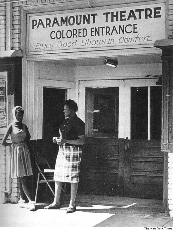 "This a black and white photo. Two African American women conversing in front of a theater where the sign states: ""Paramount Theatre, Colored Entrance, Enjoy Good Shows in Comfort."""
